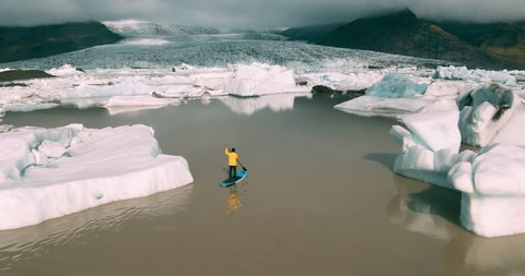 Aerial shot of man paddling stand up paddle board in glacier lagoon with giant icebergs in Iceland
