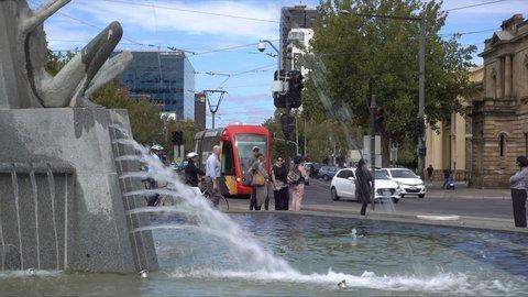 ADELAIDE, SOUTH AUSTRALIA/AUSTRALIA - MARCH 15, 2018: Tram passes Victoria Fountain at Victoria Square, Adelaide, South Australia. Victoria Square marks the centre of Adelaide.