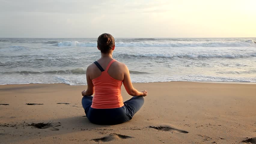 Woman doing yoga - meditate and relax in Padmasana Lotus asana pose with chin mudra outdoors at tropical beach on sunset | Shutterstock HD Video #1014949474