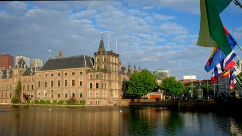 View of the Binnenhof House of Parliament and the Hofvijver lake with downtown skyscrapers in background with flags. The Hague, Netherlands