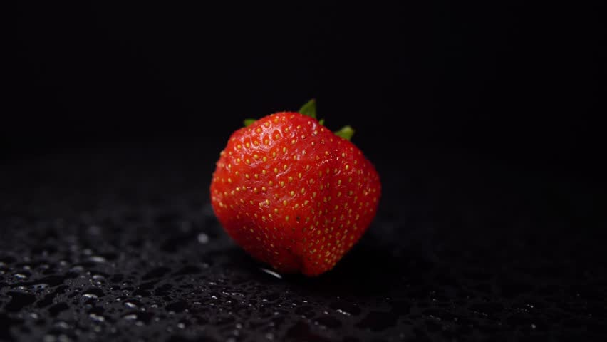 Fresh, ripe juicy strawberries with drops of water revolve. Red berry counterclockwise rotation on a black backdrop, close-up. Strawberry background, seamless looping.
