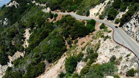 Aerial Shot Flying Over a Car Traveling Along the Side of a Mountain near Lake Arrowhead, California