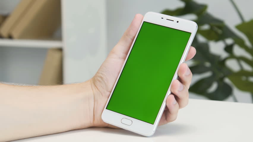 Hands using white modern smartphone with green screen in office with white walls and shelf. One swipe and touch. Close up shot. #1014992254