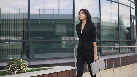 portrait of young confident business woman in suit with folder for papers in hands. a girl in a trouser suit walks down the street