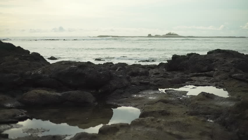 Coastal rock formations with puddles on tropical beach. Close up of rocks on Costa Rica shoreline and waves breaking.