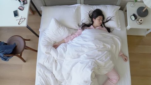 The quick movement of an Asian woman changing her sleep positions and postures when she sleeps deeply.