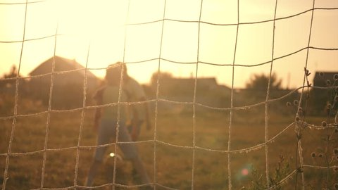 Two boys playing soccer at sunset. A soccer ball is hitting. Football goal. Children's dreams of victories