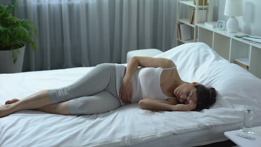 Young woman suffering from severe pain and cramp in lower abdomen, menstruation