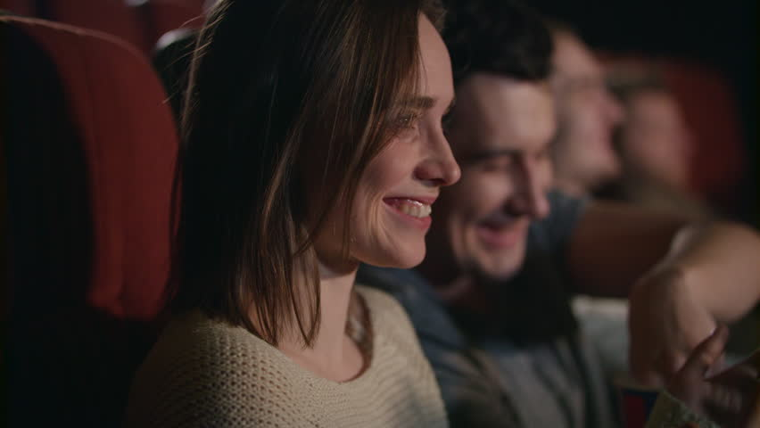 Smiling woman watching movie. Close up of beautiful girl laughing in cinema in slow motion. Boyfriend and girlfriend have fun at movie theater. Romantic date at cinema. Love couple watch comedy film