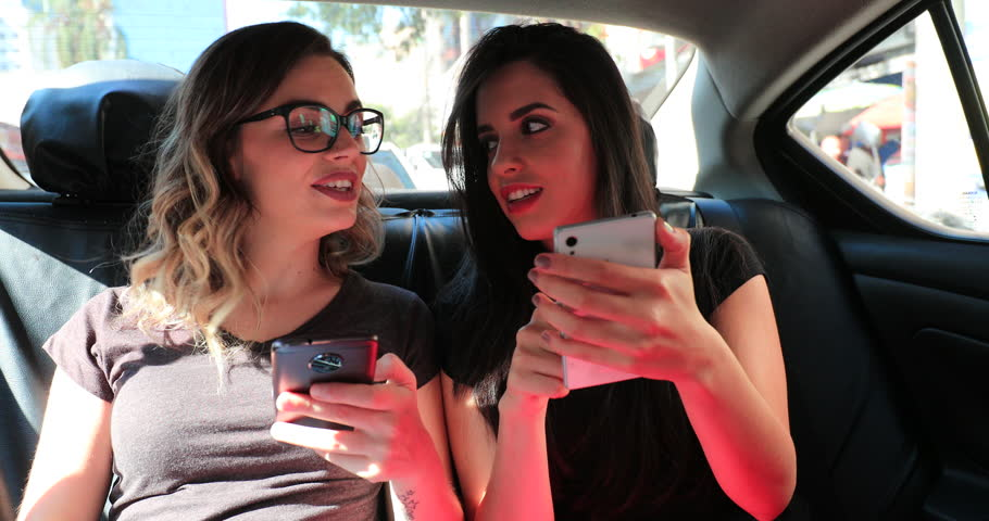 Friends looking at their cellphones in the back seat of a taxi cab gossiping and browsing the internet on their smartphones #1015061044