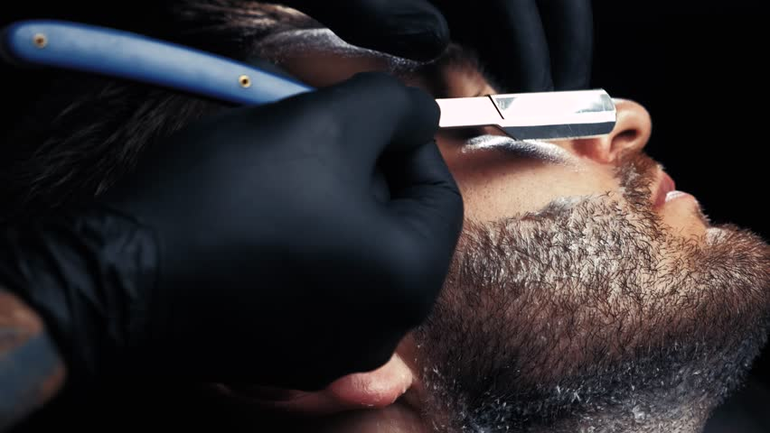 Close-up of hands in black gloves shaving the face of a man | Shutterstock HD Video #1015062454