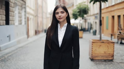 Portrait of young beautiful business woman or student in suit. She smiling, happy, standing at city center. Concept: new business, communication, banker, manager