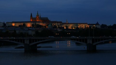 View of Prague Castle at night with cars going over a bridge in the foreground