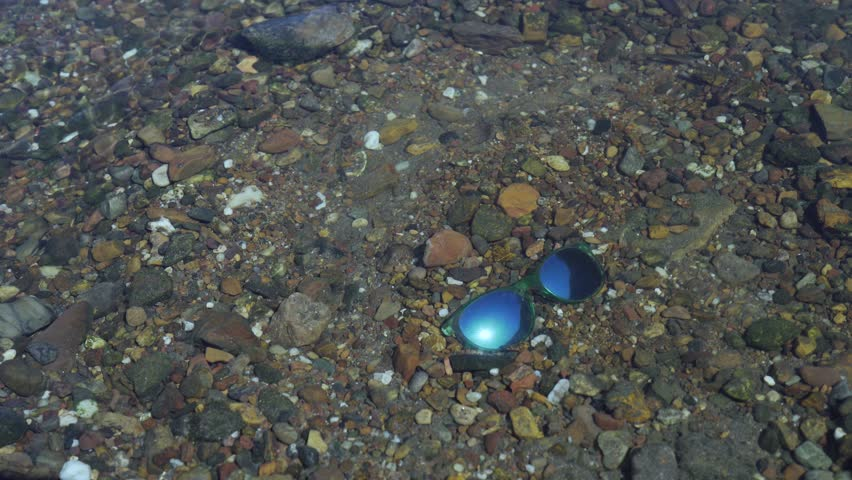 Blue sunglasses lie at a river bed and reflect the sun, small fishes swim around