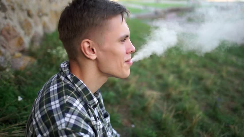 Beautiful model smokes electronic cigarette. Cute guy smiles and blows smoke from vaping. A man in a plaid shirt near the wall smokes an electronic cigarette. Handsome guy blowing smoke in the cell.
