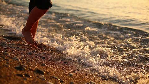 Womans legs on the beach. young woman on the sea beach enjoying sunrise in Antalya, Turkey. Woman is walking and meeting the sunrise.
