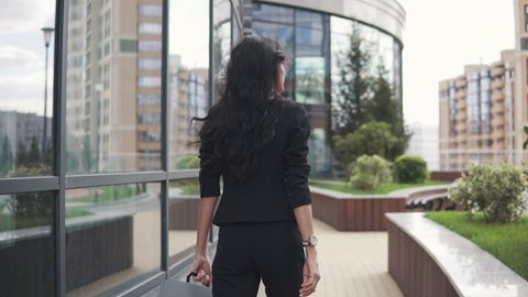 beautiful business woman in a strict suit and with a folder for papers goes near the business center. back view