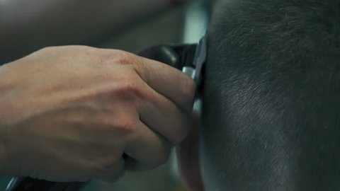 Proffesional hairdresser is cutting man's hair with electric trimmer in barber shop. Male's hairstyling in hair saloon. Slow motion.