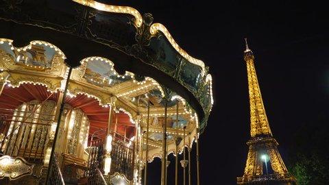 PARIS, FRANCE - AUGUST 6, 2018: Illuminated vintage carousel close to Eiffel Tower, Paris.