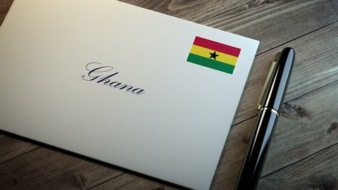 Country name written on a card or envelope in cursive font with a sleek pen on a wooden table surface under beautiful classy light. Stamp in the corner shows the flag of Ghana