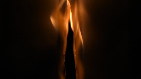 Fire in the dark in front of a black background. Fire burns a sheet of paper from center to left and right side.