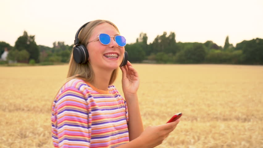 Slow motion tracking video clip of pretty blonde girl teenager young woman wearing a striped t- shirt and blue sunglasses walking listening to music on her cell phone and wireless headphones