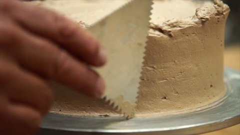 Slow motion of a baker decorating and shaping  cake