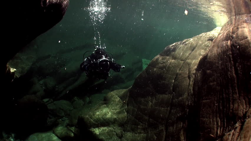 Camera operator in refraction of sunlight underwater in river Verzasca. Shooting a frame of picturesque nature on background of huge smooth stones. | Shutterstock HD Video #1015244134