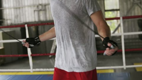 Young male boxer with his hands wrapped in bandage jumping on the skipping rope in a boxing gym. Slow motion, boxing ring on the background