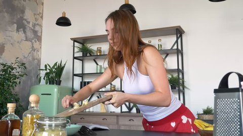 Attractive young woman with ginger hair lifting cutting board, eating banana and dropping one slice, modern kitchen in background