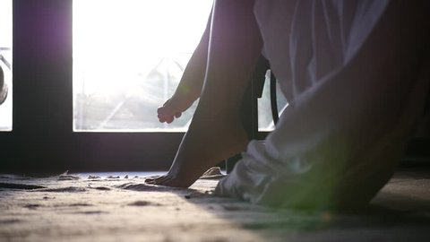 Awakening in the early morning, a girl gets out of bed, legs close-up. slow motion. 1920x1080. full hd
