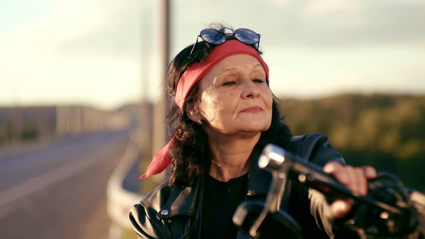 An elderly woman in a red scarf, leather jacket and gloves stands on the background of an empty road. Puts his hands on his chest and shows the sign of bikers. The woman is smiling. Happy life of an