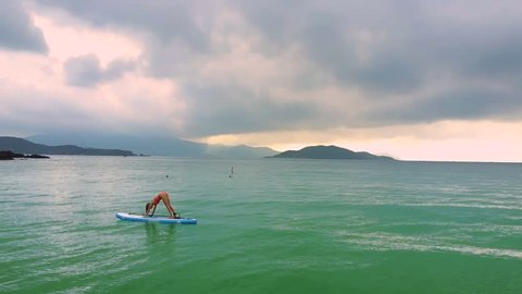 pictorial picture slim girl stands in yoga pose Forward Bend on paddleboard among azure ocean against distant islands