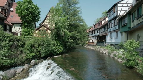 Camera pan right view of La Weiss river and old town waterfront half-timbered houses in picturesque Kaysersberg village, Alsace, France