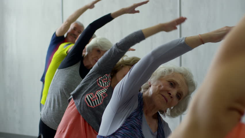 PAN of female yoga instructor and group of senior people standing in line and doing side bends with spread arms during class