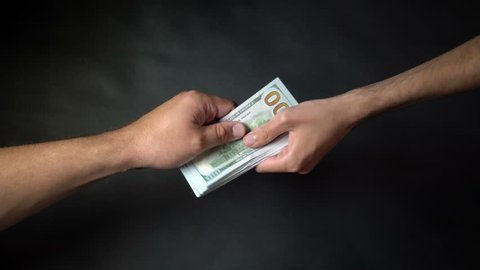 A business deal with the transfer of money on black backdrop. Dollars in hands of a close-up. People exchange money. A man gave a bundle of dollars to hands of a boy closeup on black background 4k.
