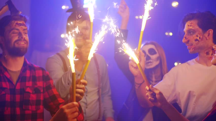 Crazy friends with sparkler dancing at the halloween party #1015346524