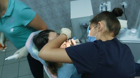 Visit to the dentist. Orthodontist doctor sets up iron braces for a woman with a dental fixator, top view