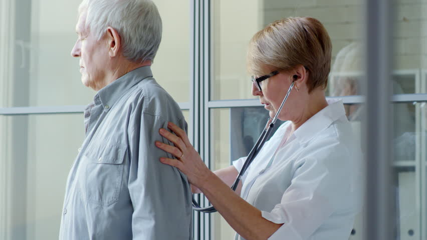 Middle-aged female doctor listening to back of elderly patient with stethoscope during physical exam in clinic | Shutterstock HD Video #1015366414