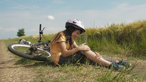 Fall from the bicycle. The child fell off the bicycle. A little girl is suffering from the pain of falling off the bike.