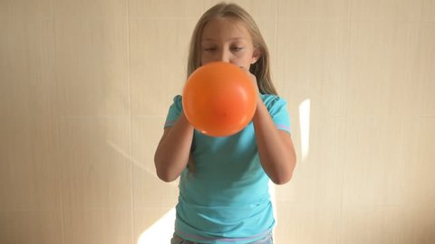 happy girl in a blue T-shirt blows bright balloon in bathroom at home. Blond boy with needle pierces a balloon. shallow focus