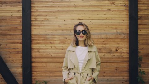 Portrait of beautiful young woman model with blond hair standing outdoors, posing and looking at camera wearing coat and sunglasses. People, fashion and beauty concept.