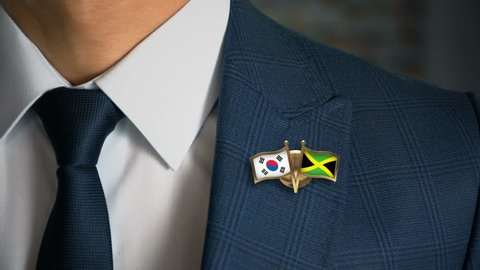 Businessman Walking Towards Camera With Friend Country Flags Pin South Korea - Jamaica