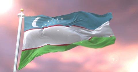 Uzbekistan flag waving at wind in slow at sunset, loop