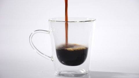Pouring coffee into glass cup on white background