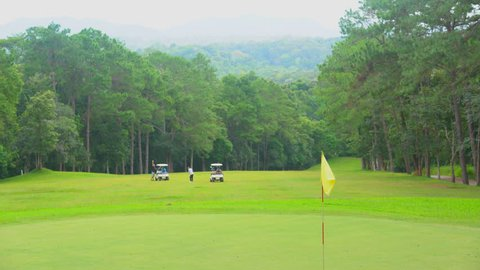 Golf sport concept, Beautiful golf course on mountain, fairway and layout beauty in forest. Flag blowing  in hole on green. Blurred golfer and golf cart on fairway playing on sunset