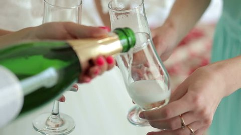 Close-up of the girl poured champagne into glasses at a bachelorette party. The bride and her friends drinking champagne at the wedding, close-up.