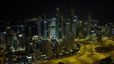 Dubai - March 2018: Aerial night view of illuminated Dubai junction Intersection Sheikh Zayed Road Skyscrapers desert traffic elevated Roads Dubai Metro Rail transport UAE RED WEAPON