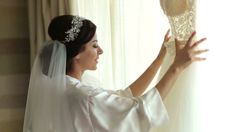 Bride in silk dressing gown holding and admiring her beautiful wedding dress in front of the window. Wedding morning, bride's preparations. Gorgeous bride in luxury dress is getting ready for wedding.