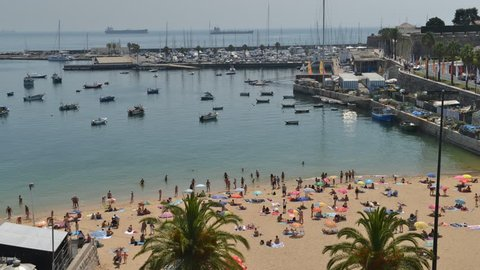 Cascais, Portugal - August 24, 2018: High vantage time lapse of crowded sandy Praia do Ribeiro and boats on bay a a sunny summer day. Cascais is a small quaint village 30km west of Lisbon